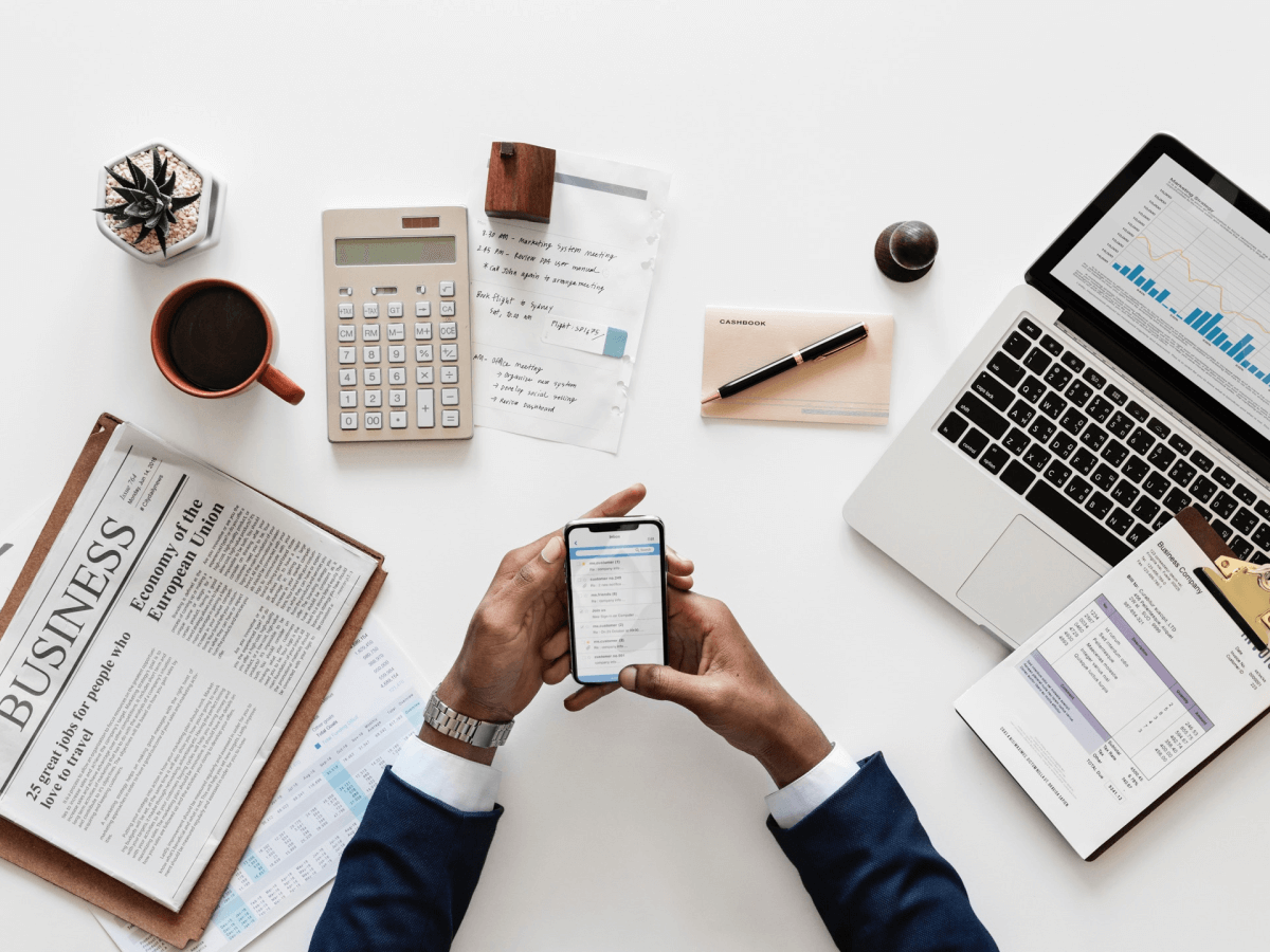Business man with laptop, newspaper, calculator and iphone x on a table